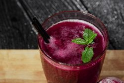 A picture of a glass of beetroot juice resembling VitalSTART with a sprig of mint