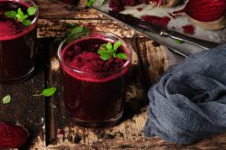 Picture of delicious nitric oxide boosting juice, with beets in the backgroundjuice,